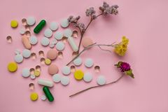 Verspreide multicolored pillen op een roze achtergrond Helende Kruiden royalty-vrije stock foto's