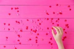 Verspreide rode harten op een heldere roze achtergrond Royalty-vrije Stock Afbeeldingen
