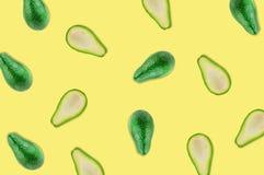 Verspreide verse wholes en de helften van organische avocado zonder pitten in centrum van gele lijst in keuken of markt stock fotografie