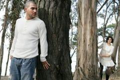 Verstecken hinter Baum Stockbild