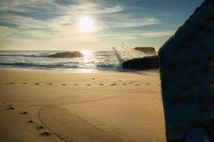 Verstecken und Beobachten hinter Blockhaus auf szenischem sandigem Strand und Brechen von Spritzenwellen gegen Blockhaus Lizenzfreie Stockfotografie
