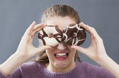 Versteckende Augen der jungen Frau des Spaßes für Ekel von fetten Bonbons Stockbild
