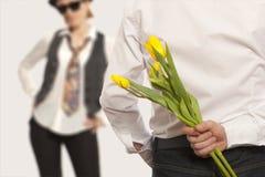 Versteckende Blumenstraußblumen des Mannes Lizenzfreie Stockfotos