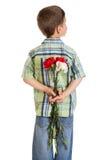 Versteckende Gartennelken des kleinen Jungen hinter sich Lizenzfreie Stockfotografie