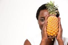 Versteckende Hälfte der schönen Afroamerikanerfrau des Gesichtes mit Ananas Lizenzfreie Stockfotos