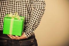 Versteckende Rückseite der Geschenkbox des Mannes hinten Feiertagsüberraschung Stockbilder