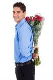 Versteckende Rosen des Mannes Lizenzfreie Stockfotografie
