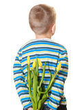Versteckender Blumenstrauß des Jungen von Blumen hinter sich Lizenzfreie Stockfotos