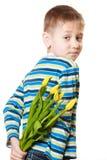 Versteckender Blumenstrauß des Jungen von Blumen hinter sich Stockfotografie