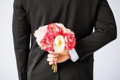 Versteckender Blumenstrauß des Mannes von Blumen Stockfotografie