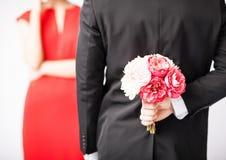 Versteckender Blumenstrauß des Mannes von Blumen Stockfotos