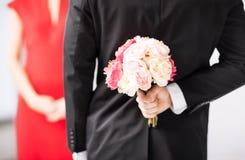 Versteckender Blumenstrauß des Mannes von Blumen Lizenzfreie Stockfotografie