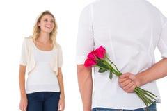 Versteckender Blumenstrauß des Mannes von Rosen von der Frau Stockfotografie