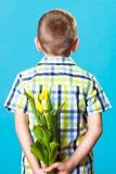 Versteckender Blumenstrauß des Jungen von Blumen hinter sich Lizenzfreie Stockfotografie
