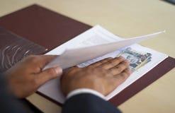 Versteckendes Bestechungsgeld des Mannes unter etwas Papieren, peruanisches Geld stockbild