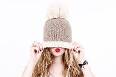 Versteckendes Gesicht der schönen blonden Frau unter einer Kappe, die einen Kuss mit den Lippen bildet stockbild