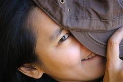 Versteckendes Gesicht der spielerischen schüchternen Frau mit Hut Lizenzfreie Stockfotos