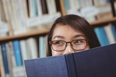 Versteckendes Gesicht des hübschen Studenten hinter einem Buch Stockbild
