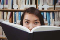 Versteckendes Gesicht des hübschen Studenten hinter einem Buch Stockbilder