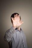 Versteckendes Gesicht des jungen kaukasischen Mannes mit der Hand Lizenzfreie Stockfotografie