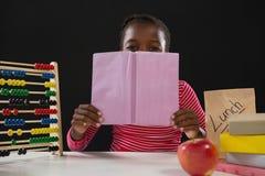 Versteckendes Gesicht des Schulmädchens hinter Buch gegen schwarzen Hintergrund Stockbild