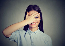 Versteckendes Gesichtslachen der schüchternen Frau schüchtern Nettes Mädchen, das durch Hand lächelt lizenzfreies stockfoto