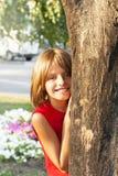 versteckt hinter dem Baum Stockbild