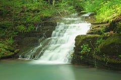 Versteckter ruhiger grüner Wasserfall Stockfotos