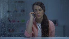 Verstoor dame sprekende telefoon op middelbare leeftijd achter regenachtig venster, slecht nieuws, gesprek stock video