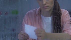 Verstoor de jonge vrouwelijke foto van de holdingsfamilie dichtbij regenachtig venster, dat aan scheiding lijdt stock video