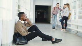 Verstoor ernstige Afrikaans-Amerikaanse mannelijke studentenzitting op vloer in universitaire gang kijkend in verschillende kante stock videobeelden