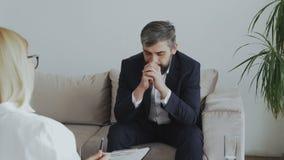 Verstoor gebaarde zakenman die over zijn problemen aan psycholoog in bureau spreken stock footage