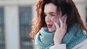 Verstoor het krullende meisje spreken op de telefoon op de straat Het haar verjaagt haar donker haar stock video