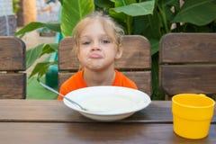 Verstoor het oude meisje van vijf jaar stelt gezichten onwillig om havermoutpap voor ontbijt te eten Royalty-vrije Stock Foto's