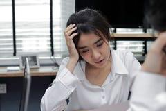 Verstoor jonge Aziatische bedrijfsvrouw die aan streng probleem tussen vergadering in bureau lijden stock foto's
