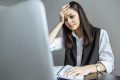 Verstoor jonge vrouw die haar hoofdzitting in de werkplaats houden royalty-vrije stock foto