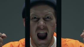 Verstoor misdadiger die met littekens op de gevangenisbars van de gezichtsholding, over verleden betreuren stock video