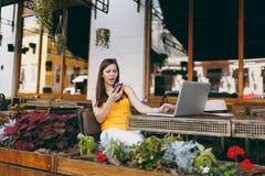 Verstoor in openlucht droevig meisje die in de zitting van de straatkoffie met laptop de computer van PC, op mobiel telefoon text stock foto