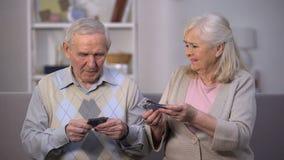 Verstoor oud paar die weinig dollarbankbiljetten, niet genoeg geld voor voedselbetaling houden stock footage