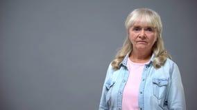 Verstoor oude vrouw die camera, concept onderzoeken lage sociale steun in pensionering royalty-vrije stock foto's