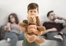 Verstoor weinig jongen die stuk speelgoed konijntje koesteren terwijl zijn ouders die alcohol drinken stock afbeeldingen