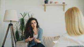 Verstoor zenuwachtig meisje die overleg binnen met professionele vrouwelijke psycholoog in psychotherapist bureau hebben stock footage