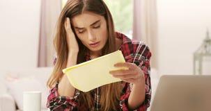 Verstoord brunette met calculator die rekeningen betalen stock video