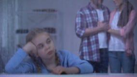 Verstoord meisje achter regenachtig venster, pleegouders die kind komen goedkeuren stock video