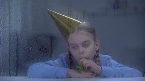 Verstoord meisje in blazende de partijhoorn van de verjaardagshoed op regenachtige dag, die alleen vieren stock footage