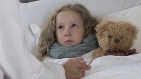 Verstoord meisje die in bed liggen, op hoge temperatuur hebben en arts bekijken stock footage