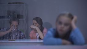 Verstoord meisje die door regenachtig venster, ouders kijken die wodka op achtergrond drinken stock footage
