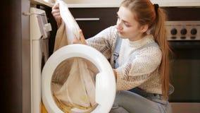 Verstoord meisje die op handdoeken na wasserij kijken stock videobeelden