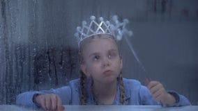 Verstoord meisje in kroon met magische stokzitting alleen achter regenachtig venster stock video