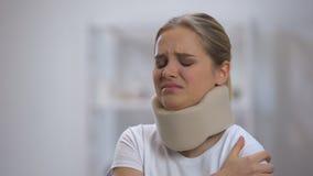 Verstoord meisje in schuim cervicale kraag die aan pijn in rug en schouder, verwonding lijden stock video
